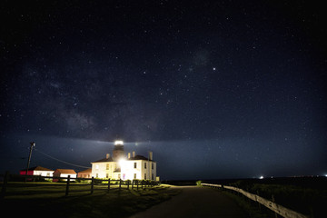 Illuminated lighthouse in the field against starry sky at night