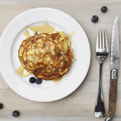 Overhead view of pancake with blueberries served in plate on table