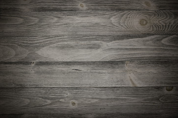 Old weathered wood surface with long boards lined up. Wooden planks on a wall or floor with grain and texture. Dark neutral tones with contrast.
