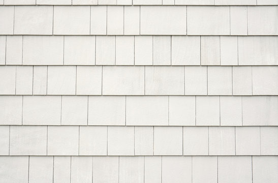 Neutral white or tan siding on a house or building. Straight parallel lines. Outdoor siding with highlights.. Roofing or construction material.