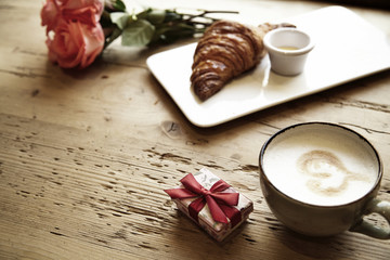 Fresh bakery croissant, coffee with heart sign, rose flowers on wooden table. Romantic breakfast for Valentine's Day celebrate concept. Focus on box