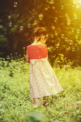 Asian girl playing with soap bubbles on nature background. Outdoors.