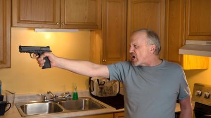 Man with handgun in kitchen