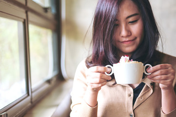 A beautiful asian woman looking at hot coffee with whipped cream topping in the cafe