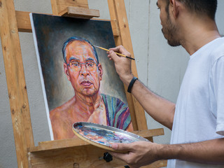 Artist painting portrait of asian man,oil color on canvas