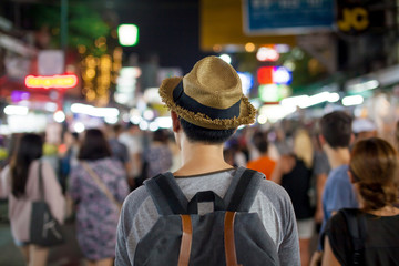 Young Asian traveling backpacker in Khaosan Road night market