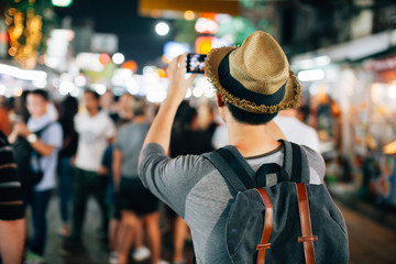 Young Asian traveler taking photo with mobile phone in Khaosan road