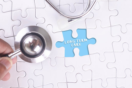 Doctor holding a Stethoscope on missing puzzle WITH LONG TERM CARE