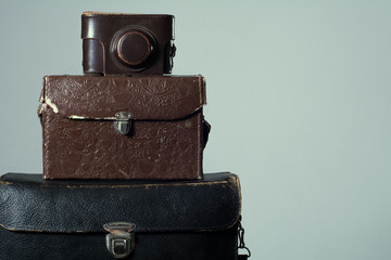 Background stack of old shabby suitcase with a camera in bag.