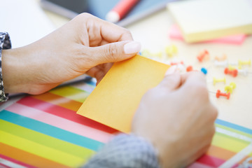 Woman at office holding adhesive note