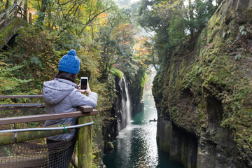 Woman using cellphone to taking photo in Takachiho Gorge