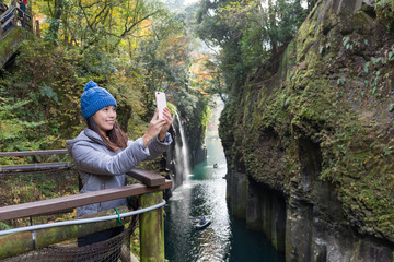 Woman using cellphone to taking selfie in Takachiho Gorge