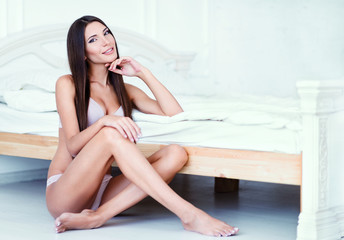 Attractive sexy young woman in underclothes sitting at bed