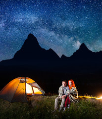 Sweety couple tourists covered with a plaid sitting together near campfire and shines tent at night. High mountains, starry sky, Milky way on the background