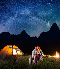 Happy couple tourists covered with a plaid sitting together near campfire and shines camp at night under stars and looking to the starry sky and Milky way. Silhouette of high mountains on background