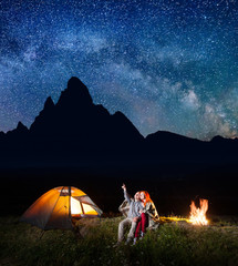 Tourist man showing red-haired woman at the stars in the sky. Couple sitting near the camp on the background silhouette of the high mountains at night