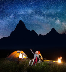 Male backpacker showing his girl at the stars and Milky way in the night sky. Happy couple covered with plaid sitting near the glowing tent and campfire. On the background silhouette of the mountains