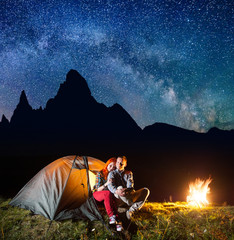 Night camping. Romantic couple sitting in front tent near campfire under shines starry sky and Milky way. On the background silhouette of the high mountains. Long exposure