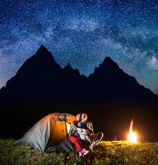Two hikers having a rest in his camp at night near campfire under shines starry sky on the background silhouette of the mountains. Astrophotography