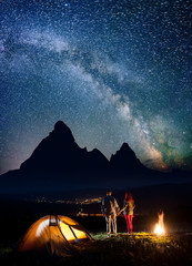Romantic tourist family - man and woman holding hands, standing near campfire and enjoying beautiful starry sky and Milky way. Silhouettes of the mountains and luminous village in the valley