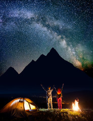 Happy pair backpackers raised their hands up under the stars near camping, looking on incredibly beautiful starry sky, the silhouettes of the mountains and luminous village in the valley at night