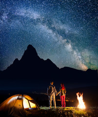 Rear view happy tourist family - man and woman holding hands, standing near tent and campfire, enjoying incredibly beautiful starry sky and Milky way, silhouettes of the mountains. Long exposure