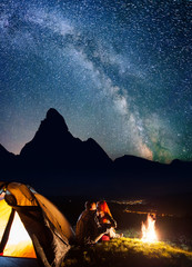 Night camping. Loving couple backpackers sitting and kissing near a campfire and tent under the stars and Milky way. On the background silhouette of mighty mountains and luminous village in the valley