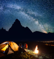 Night camping. Romantic couple sitting face to face in front tent near campfire under shines starry sky. On the background silhouettes of the high mountains and luminous village in the valley