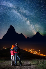 Romantic couple hugging each other, standing on a hill under the bright stars and Milky way, looking on the silhouettes of the mountains and luminous village in the valley at night. Long exposure