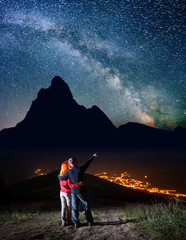 Guy hugging red-haired girl and shows on stars and Milky way in beautiful starry sky at night against silhouettes of the high mountains and luminous village in the valley. Long exposure. Low light