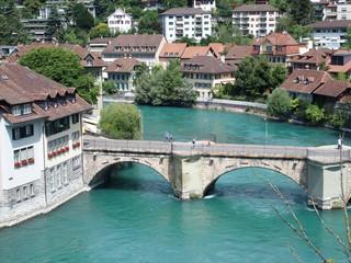 Stony bridge over clean alpine river in city of Bern