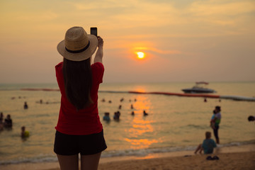 traveler girl use smartphone take photo sunset with blur tourist at playing sea