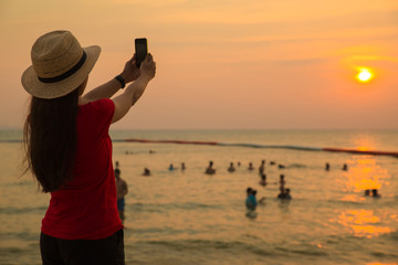 Girl relax by take photo sunset in sea beach