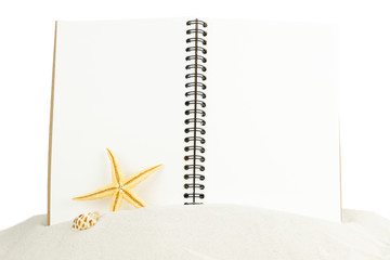 Notebook with starfish on sand isolated on white background.