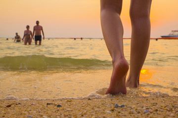 leg barefoot going to sea with sunset time
