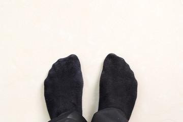 businessman feet in black socks on floor