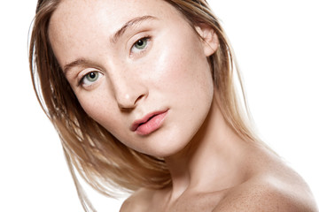 woman with freckles on her face with a light sensitive skin. Portrait with bare shoulders on a white background