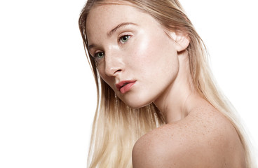 Young woman with freckles on his face and body with light sensitive skin. Portrait with bare shoulders on a white background