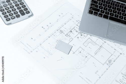 Calculator And Notebook Over House Construction