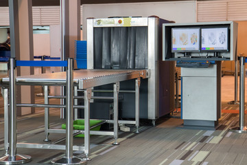 X-ray scanner and metal detector with monitor at airport security checkpoint