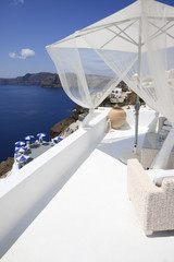 City of Oia on Santorini Island (part of the Cyclades). White terrace with seating furniture and parasol located at the Caldera (volcano rim) and overlooking the Mediterranean sea.