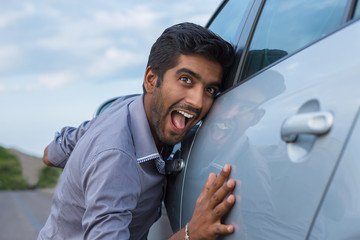 Happy excited young indian man driver embracing petting his car. Green energy biofuel electric environment friendly new car concept.