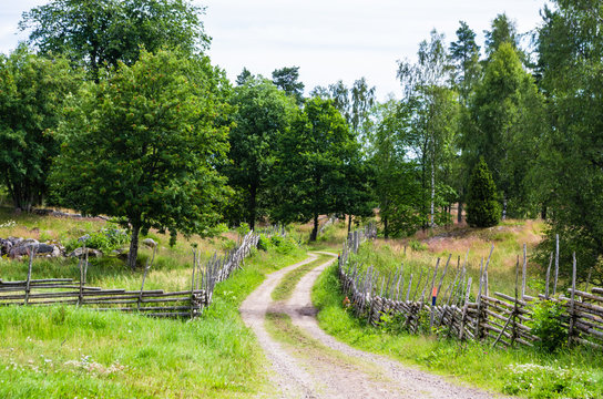 Gravel road in a rural landscape in the countryside with meadows surrounded with wooden fences in summer.