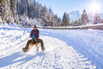 Cheerful girl riding a sled downhill, snow, sunny winter landscape