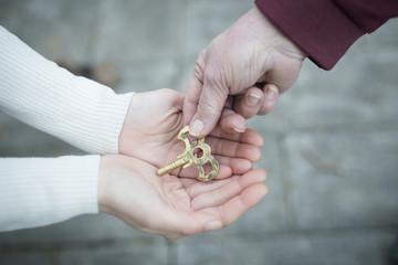 鍵を手渡す親子の手