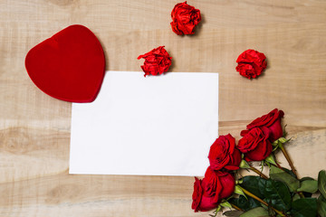white sheet of paper, red heart, bouquet of red roses lie on a w