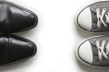 An elegant business shoe (oxford style) and a casual shoe facing each other. Use as symbol for the concept 'work life balance'. Copy space in the middle.