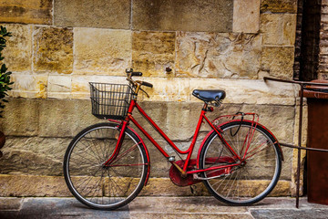 Red old bicycle over stone wall.