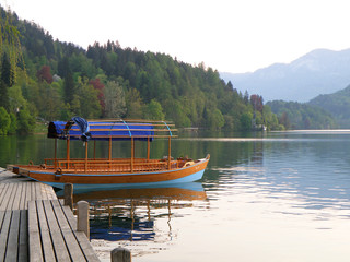 One blue and brown colored boat moored at the pier on Lake Bled, Slovenia