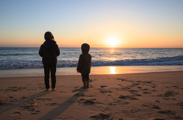 Two kids standing on sandy beach and enjoying sunset, Algarve, Portugal